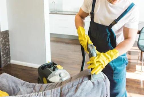 работник чистит спинку дивана