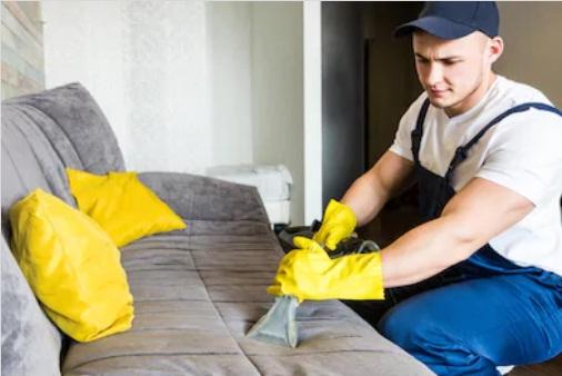 работник чистит сиденье дивана